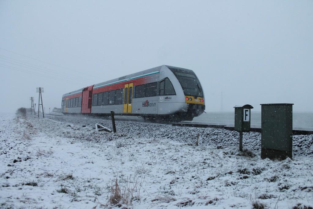 Im Schneetreiben am 24.01.2014 passiert ein GTW 2/6 der HLB den ehemaligen Bahnübergang zwischen Lich und Langsdorf auf der Lahn-Kinzig-Bahn.