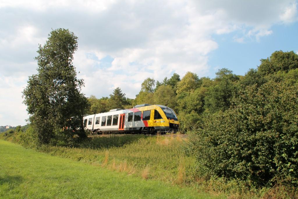 Aus dem Gebüsch zwischen Runkel und Villmar auf der Lahntalbahn schaut am 01.08.2015 ein LINT der HLB hervor.