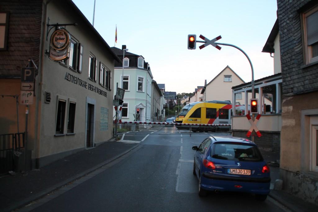 Nach einem Halt in Runkel überquert ein LINT der HLB am 01.08.2015 den Bahnübergang der Lahntalbahn.