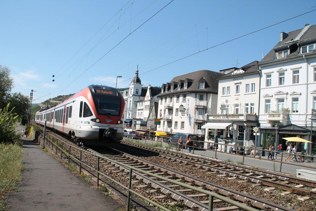 Ganz in weiß, mutet der Nahverkehr in Rüdesheim an. Am 30.08.2015 durchquert die VIAS mit einem FLIRT den Weinort in Richtung Frankfurt.