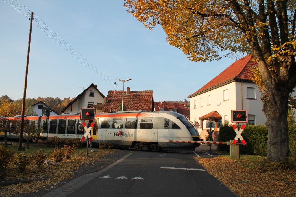 642 406 der HLB überquert am 31.10.2015 den Bahnübergang in Königshofen auf der Kahlgrundbahn.