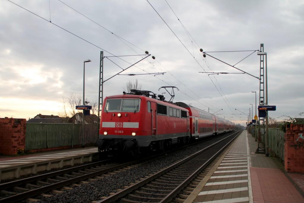 111 063 legt mit ihrem Zug aus Doppelstockwagen einen kurzen Halt in Bürstadt auf der Reitbahn ein, aufgenommen am 21.11.2015.