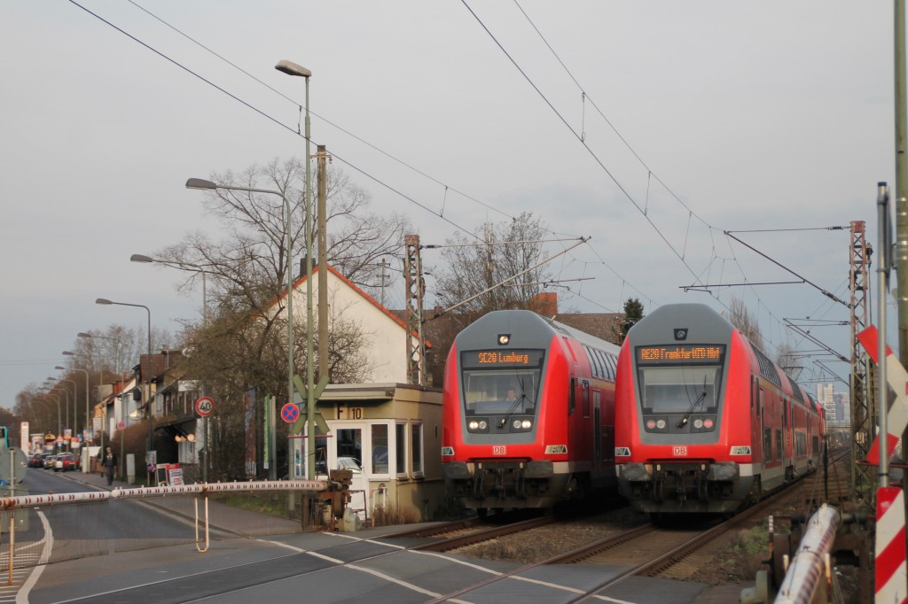 Begegnung zweier Doppelstockzüge am Bahnübergang in Frankfurt-Nies, aufgenommen am 26.02.2016.