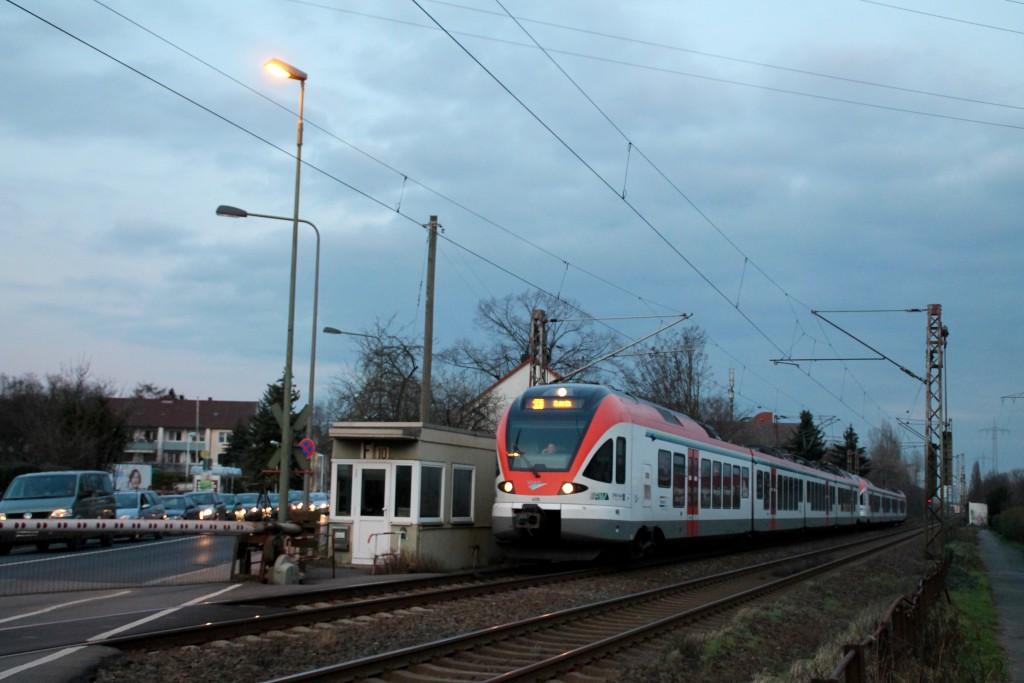 Ein FLIRT der VIAS überquert im Abendlicht den Bahnübergang in Frankfurt-Nied, aufgenommen am 26.02.2016.
