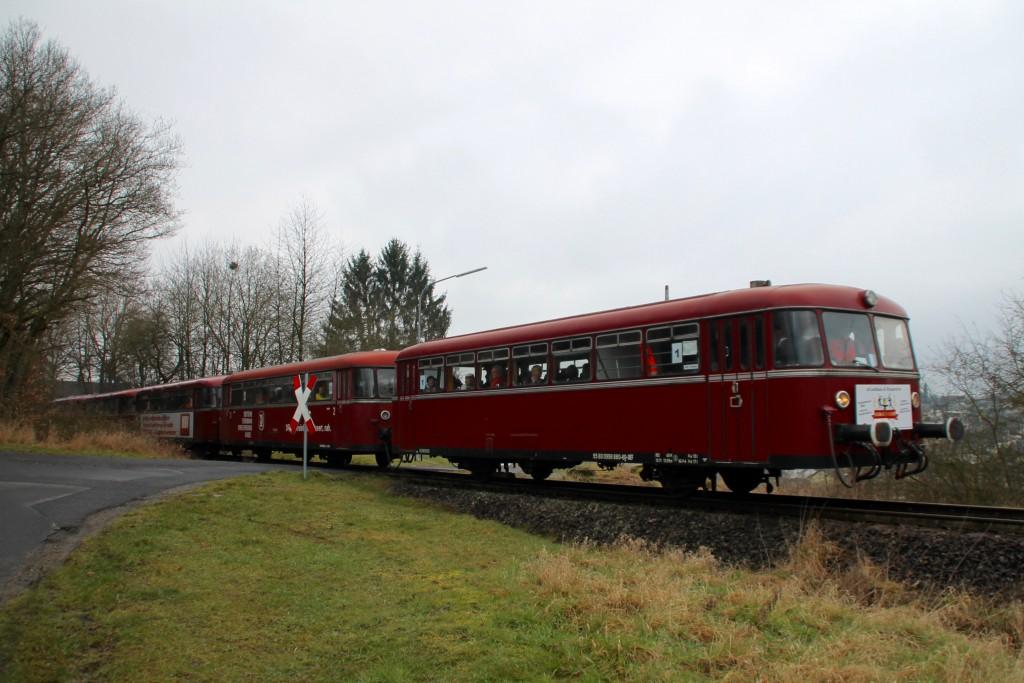 998 880, 998 250, 798 818, 798 622 und 796 724 an einem unbeschrankten Bahnübergang bei Mogendorf auf der Holzbachtalbahn, aufgenommen am 06.03.2016.
