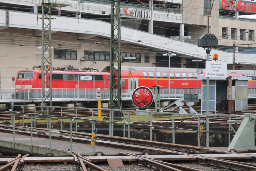 Hinter der Siegener Drehscheibe erreicht eine 111 mit ihrem Zug aus Doppelstockwagen den Bahnhof Siegen, aufgenommen am 27.03.2016.
