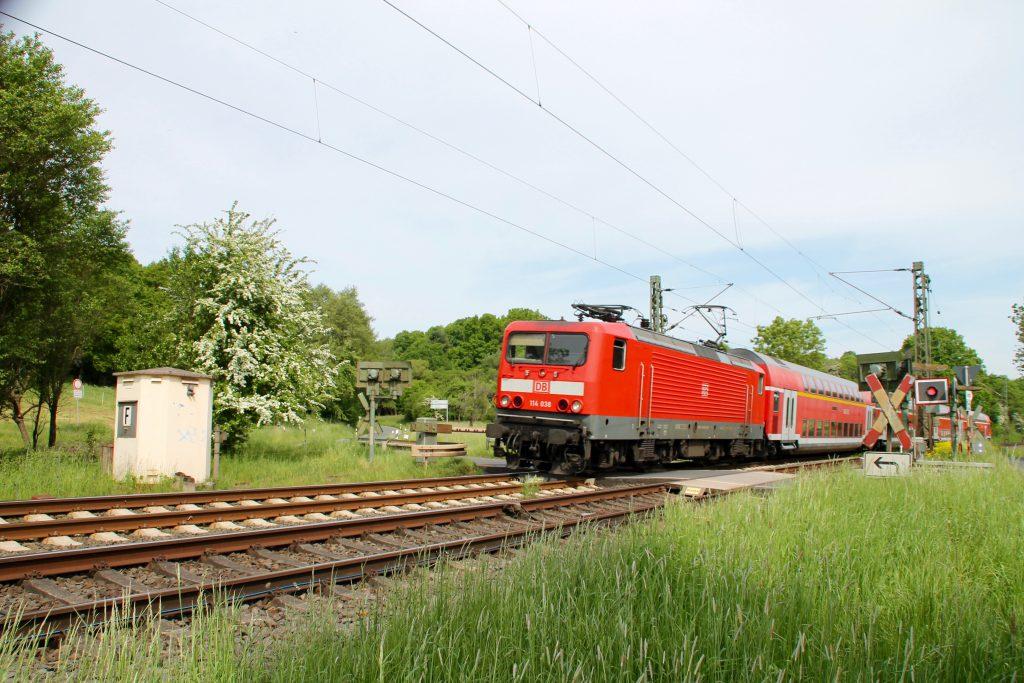 114 038 überquert mit ihrem Zug den Bahnübergang bei Dillheim auf der Dillstrecke, aufgenommen am 22.05.2016.