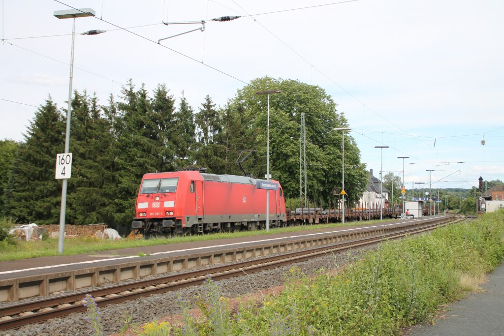 185 381 jagt mit ihrem Güterzug durch den Bahnhof Dutenhofen auf der Dillstrecke, aufgenommen am 29.06.2016.