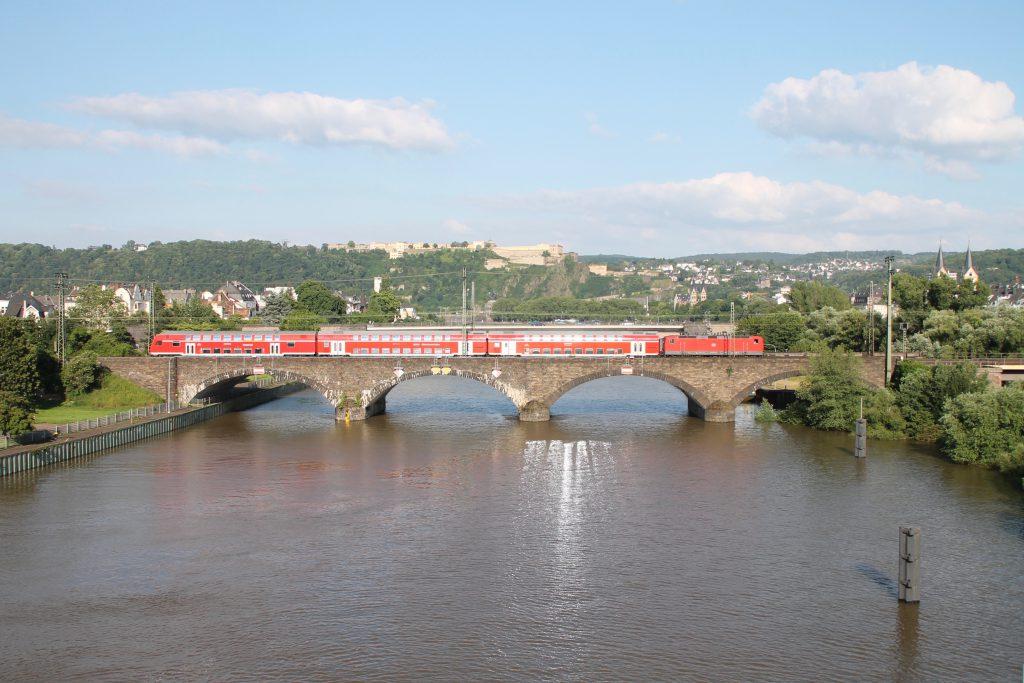 Eine 143 überquert mit ihren Doppelstockwagen die gemauerte Moselbrücke in Koblenz auf der linken Rheinstrecke, aufgenommen am 19.06.2016.