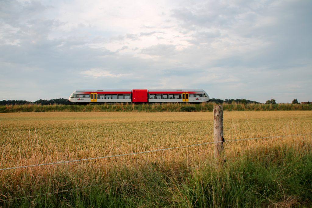 Ein GTW der HLB durchquert im Abendlicht die Felder bei Hungen auf der Lahn-Kinzig-Bahn, aufgenommen am 10.07.2016.
