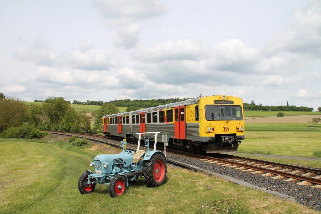 Ein VT2E der HLB begegnet einem Eicher Traktor in Hundstadt auf der Taunusbahn, aufgenommen am 21.05.2016.